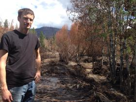 Rory Williams stands near his farm in front of Benson Creek. The creek is normally a trickle in August; it overflowed Thursday night in a flash flood.
