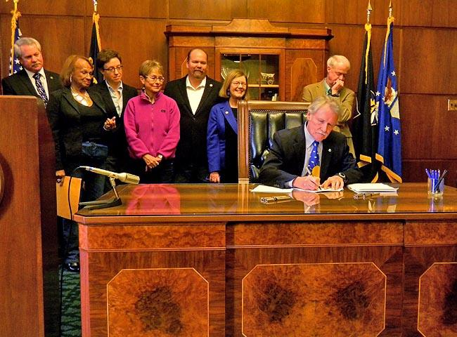 Oregon Governor John Kitzhaber signing two measures into law in March.
