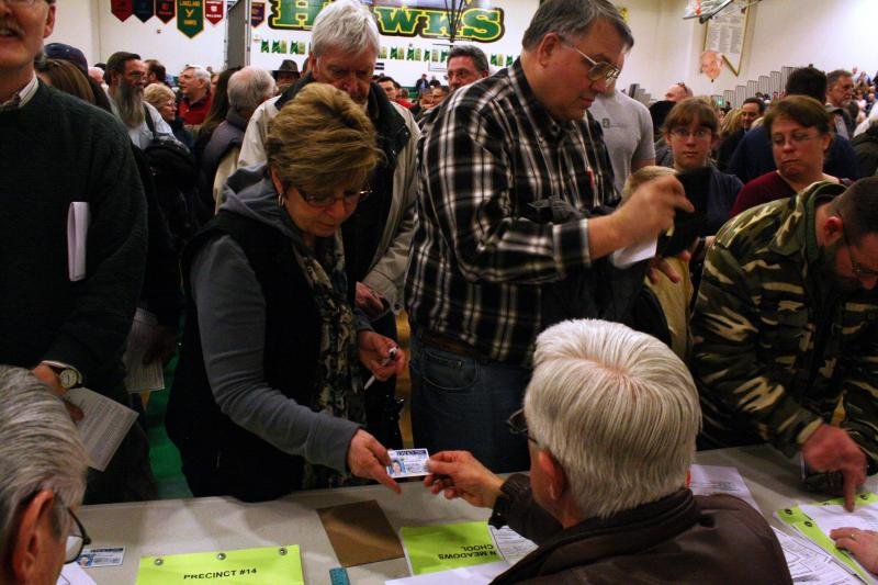 Idaho Republican voters confirm their registration at a presidential caucus site Tuesday night in Rathdrum, Idaho.
