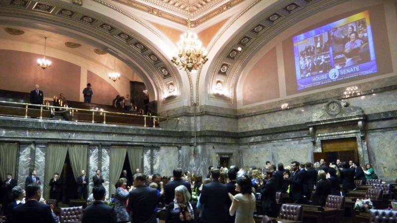 Legislators and staff celebrate on the Senate floor after adjournment.