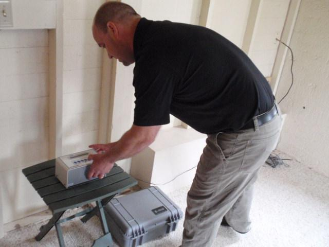 Neal Correy of EcoTech checks a radon monitor in the basement of the Oregon governor's mansion in Salem.