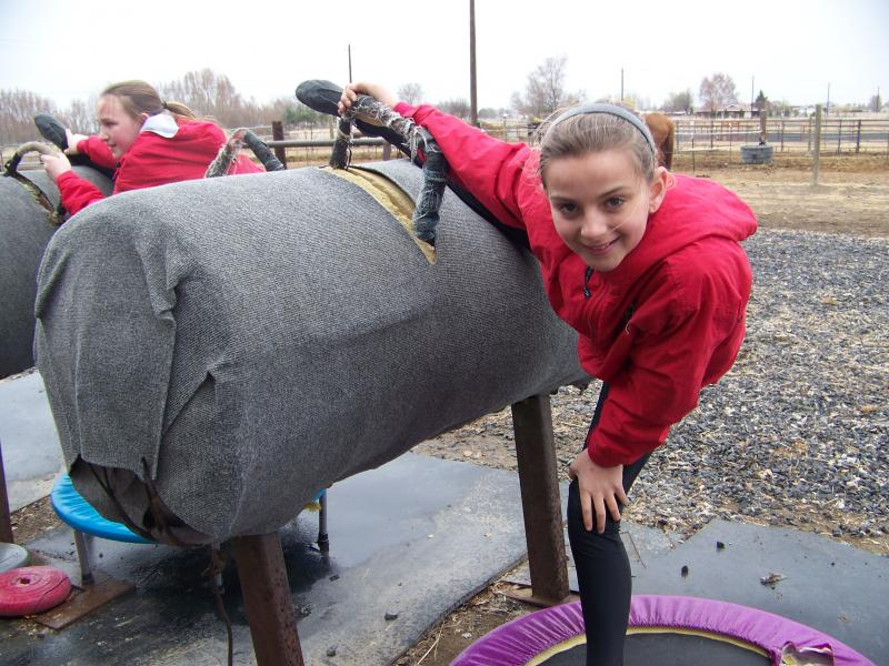 Jazmyn Wentland, 10, and the other vaulters on her team warm up with stretches and practice on a barrel before they do their routines on horses in Moses Lake, Wash.