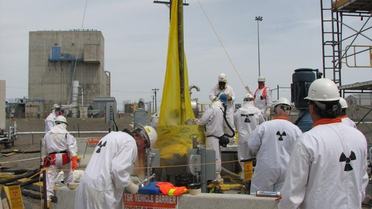 Workers at Hanford remove low-activity waste from a tank.