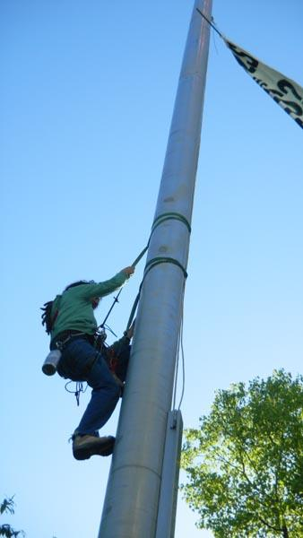 Perry Graham climbs down a flagpole at the Oregon state capitol after hanging a banner protesting logging on state owned forest land.