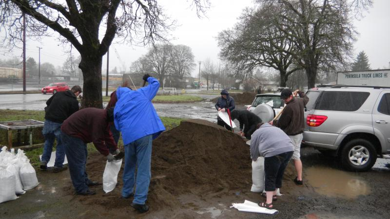 People fill sandbags at a City of Salem maintenance facility.