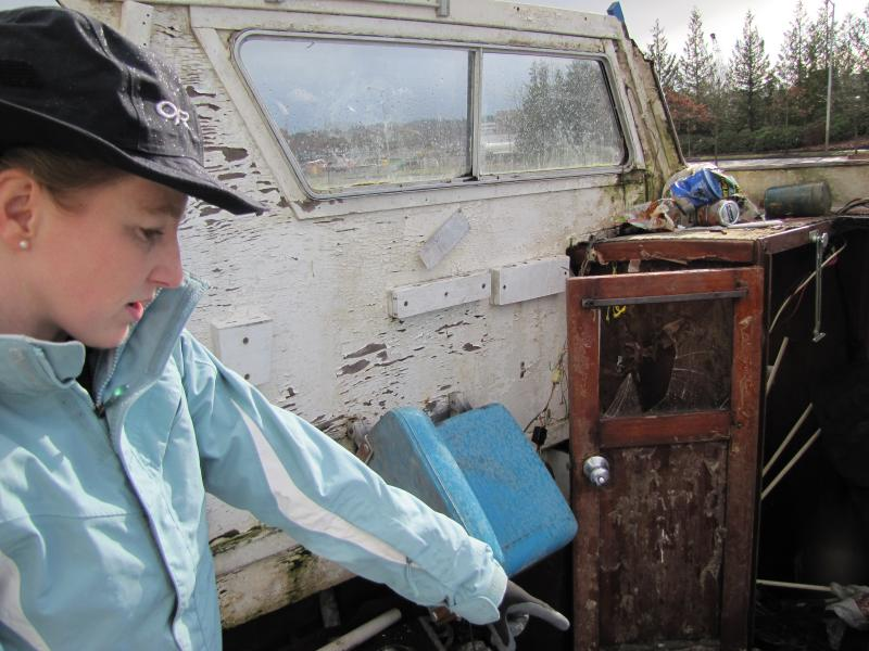 "Melissa Ferris heads the Derelict Vessel Program in Washington. She's standing on the ""deck"" of a cabin cruiser that was dredged from the bottom of an inlet near Olympia."