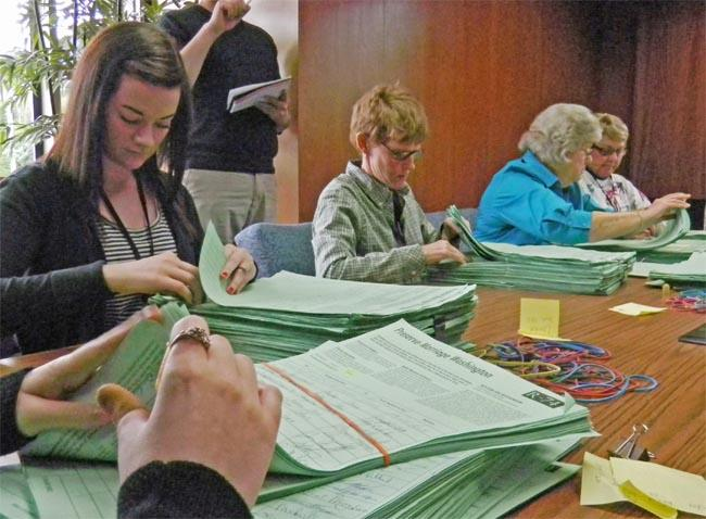 Workers at Washington's Secretary of State's office begin to count R-74 petitions.