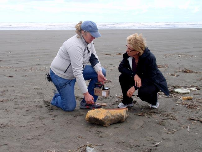 Radiation Health Physicist Lynn Albin and Wash. Gov. Chris Gregoire check a piece of marine debris.
