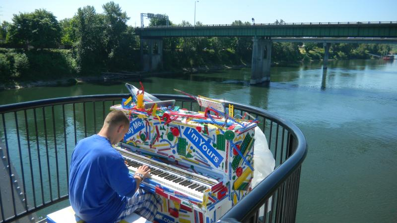 Michael Condash plays a tune on a piano located halfway across the Union Street pedestrian bridge in Salem.