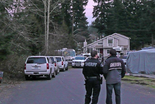 A Pierce County Sheriff's deputy stands guard outside the house where Josh Powell killed himself and his two young sons in February.