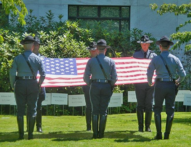 "Oregon State Police officers perform a ""ceremonial flag fold"" at the future site of the Oregon State Police memorial."