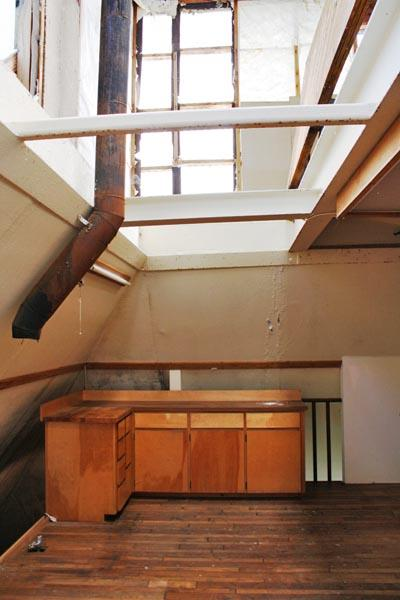 This pyramid shaped home in north Idaho was built out of concrete and steel beams, entirely underground. In this picture, an open hatch above the kitchen allows natural light in.