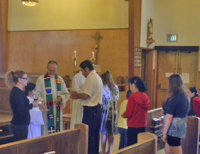 The Reverand Kurt Neilson leads communion at a Spanish language mass at Saints Peter and Paul Episcopal Church in Portland.