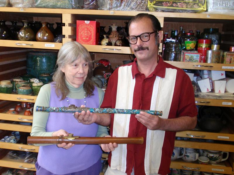 Donor Steven Martin and UI curator Priscilla Wegars hold antique opium pipes.