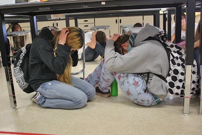 Students at Chinook Middle School in Lacey, Wash., take cover and brace during the Great ShakeOut drill.