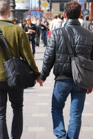 Photo of two men holding hands.