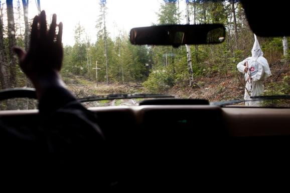 Shaun Patrick Winkler waves to Mark Eliseuson while entering his compound on the evening of a cross burning cermony near Priest River, Idaho.