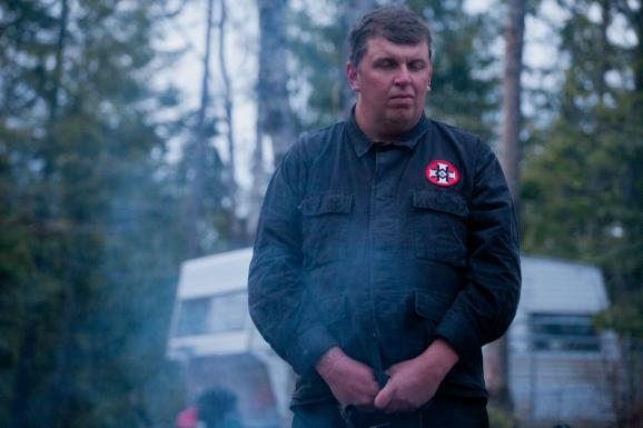 Shaun Patrick Winkler stands beside a fire at his compound near Priest River, Idaho.