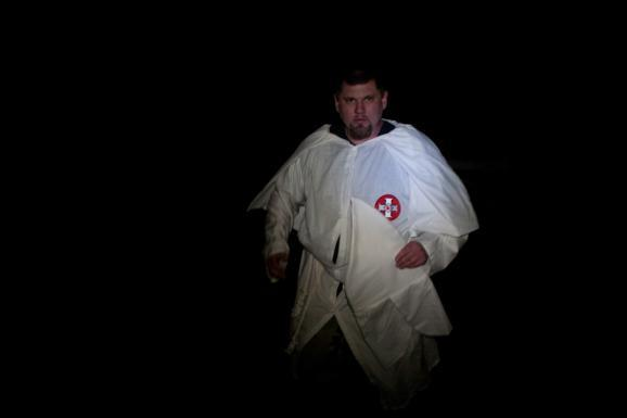 Mark Eliseuson is a fellow Klan member of Winkler's. He walks through the darkness in his KKK robe prior to a cross burning ceremony at Winkler's compound near Priest River, Idaho.