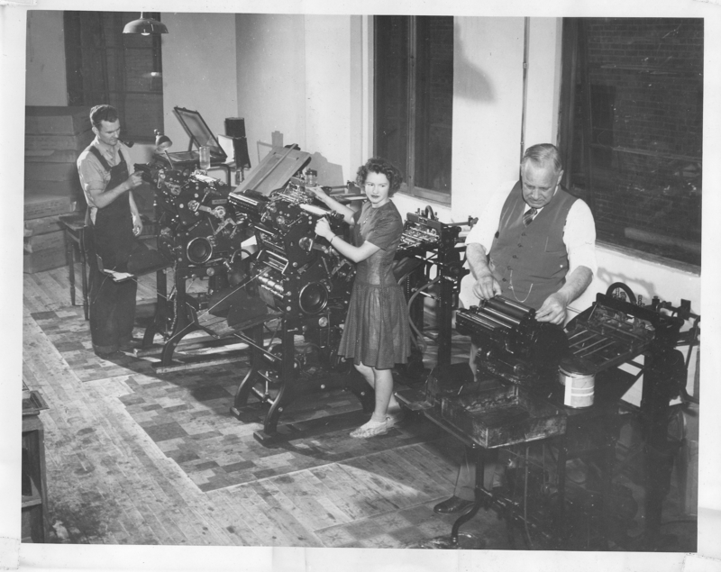 Frank Robnison examining a printing machine at the Psychiana printing department.