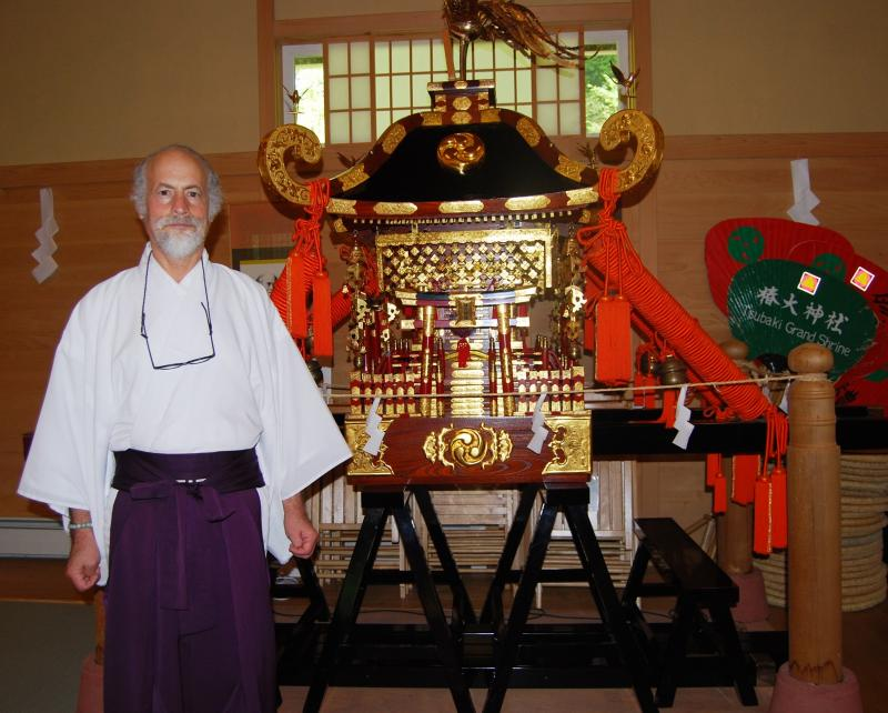Rev. Barrish stands next to a Mikoshi, a palanquin to carry a spirit. Mikoshi translates to portable Shinto shrine.