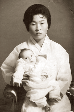 Joel Peterson's Korean mother holding him as an infant.