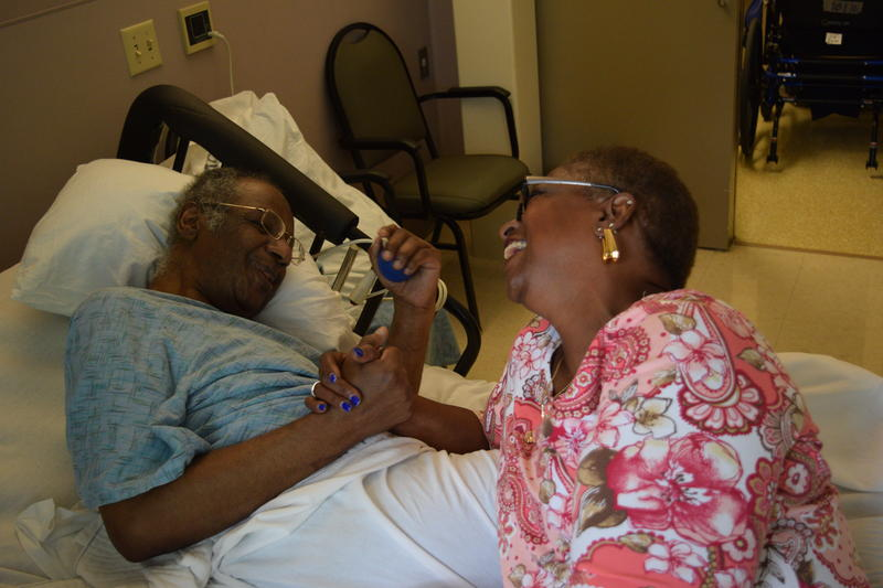 Drea Lake laughs and dances around the bed to Kool and the Gang at the nursing home where her husband Tyrone lives.
