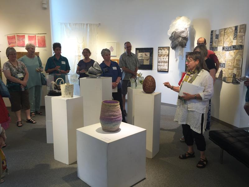 "Layne Goldsmith discusses one of the works of art, ""The Birth of the Grid"" by Nancy Loorem Adams, at the ""Fiber Fusion"" gallery opening in the Tri-Cities. The piece won the Jurors Award"