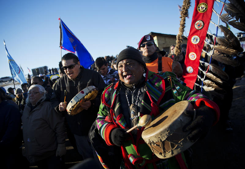 Dan Nanamkin, of the Colville Nez Perce Native American tribe in Nespelem, Wash., right, drums with a procession through the Oceti Sakowin camp after it was announced that the U.S. Army Corps of Engineers won't grant easement for the DAPL.
