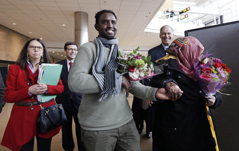 Isahaq Ahmed Rabi, center, holds the hand of his wife, Ibado Hassan, in tears at right, as they walk with his lawyer Carol Edward, left, Attorney General Bob Ferguson and Washington Gov. Jay Inslee shortly after Rabi's arrival Monday, Feb. 6.