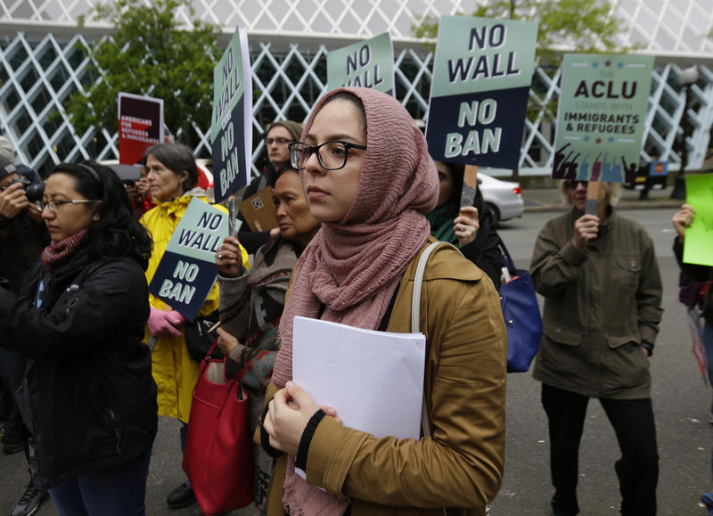 The organizing director of Americans for Refugees and Immigrants waits for her turn to speak during a demonstration against the revised travel ban outside a Seattle federal courthouse.