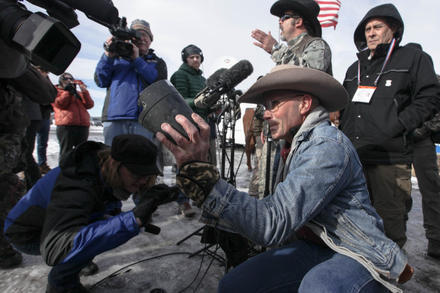"""Robert """"LaVoy"""" Finicum holds up an FBI surveillance camera the occupiers dismantled during their time at Malheur National Wildlife Refuge."""