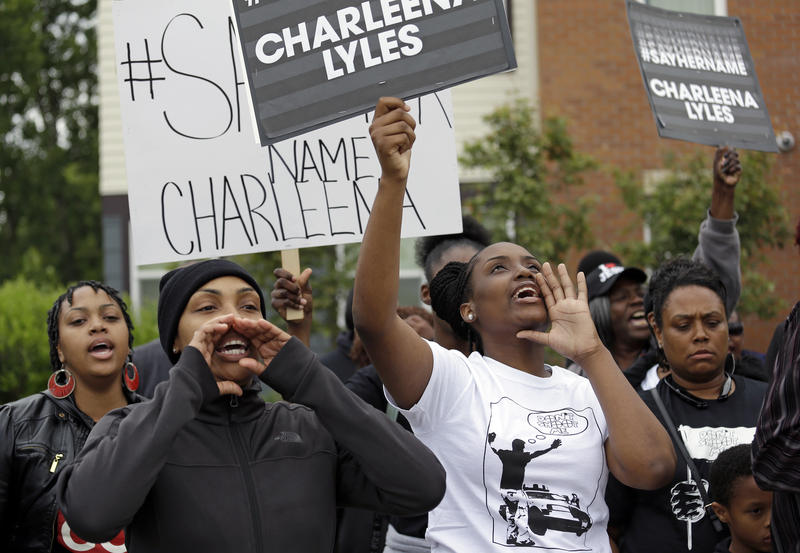 Relatives and friends of Charleena Lyles, a pregnant mother who was shot and killed by police, chant at a gathering near the place she was killed, Tuesday, June 20, 2017, in Seattle.