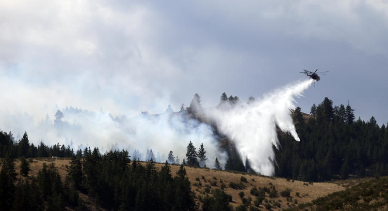 A firefighting helicopter drops water on blazing trees Friday, Aug. 21, 2015, in Okanogan County.