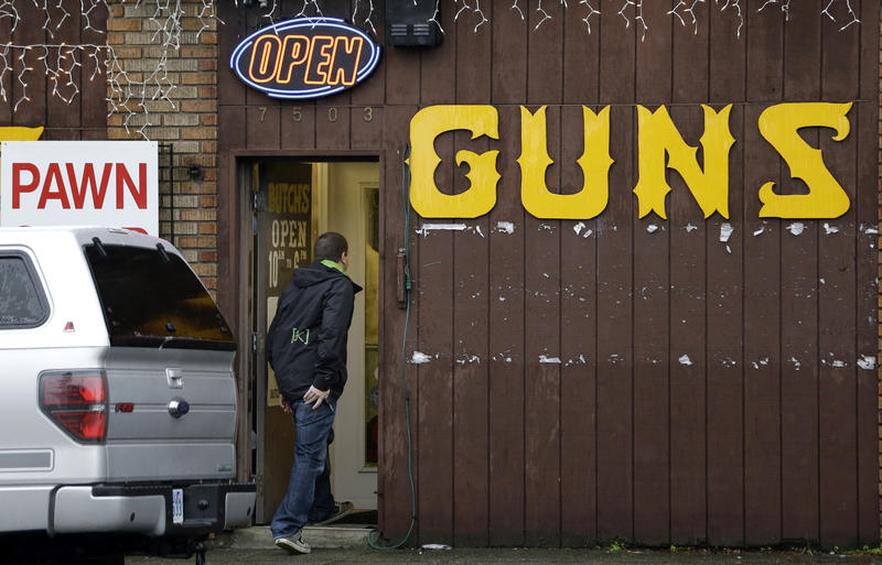 "This Dec. 19, 2012 file photo shows a man walking into a gun shop in Seattle. The Washington Supreme Court upheld Seattle's so-called ""gun violence tax"" against a challenge from gun-rights groups Thursday Aug. 10, 2017."