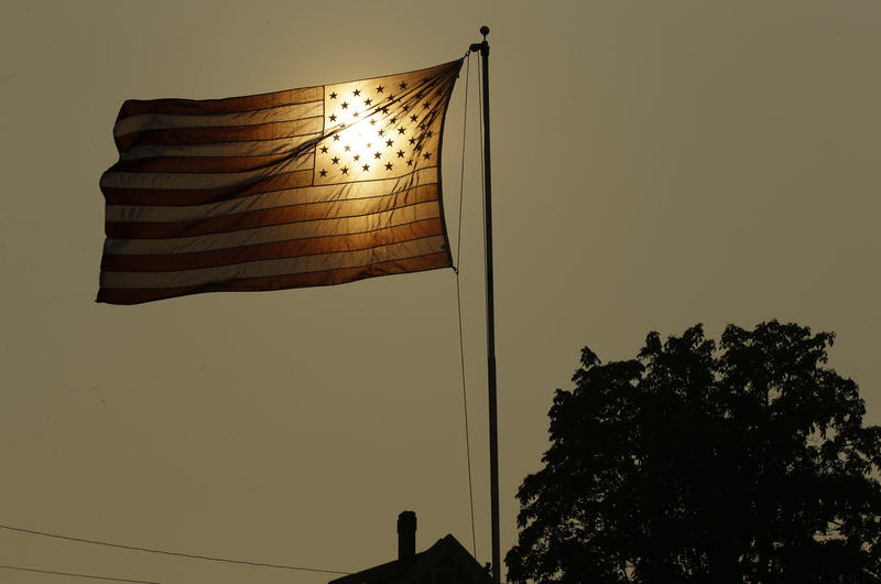 The evening sun shines through a U.S. flag flying in the wind against a sky made hazy with smoke from wildfires, Wednesday, Aug. 2, 2017, in Tacoma, Wash.
