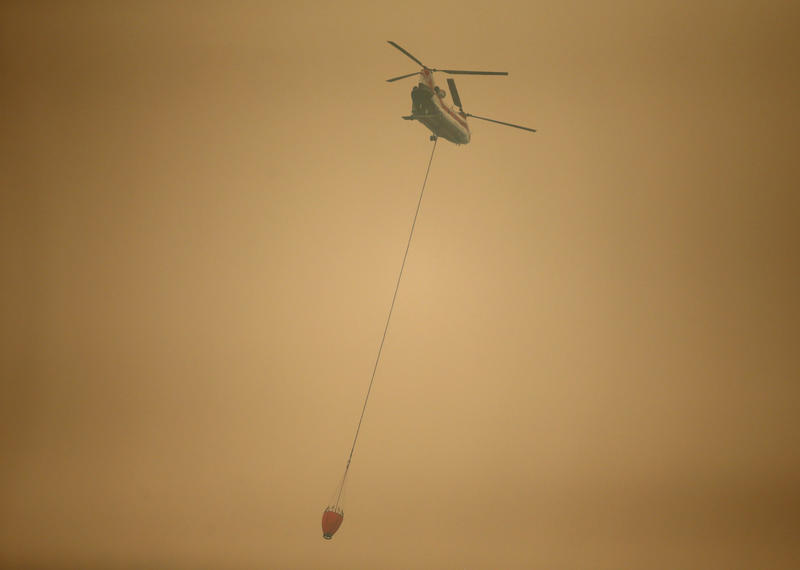 A helicopter flies through dense smoke with a water bucket near Stevenson, Washington, Wednesday, Sept. 6, 2017, as it works to battle the Eagle Creek Fire at the Columbia River Gorge.
