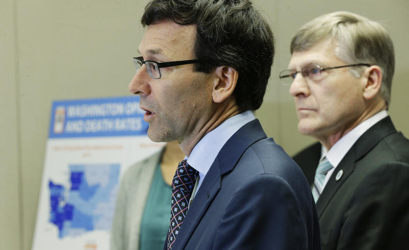 Washington Attorney General Bob Ferguson, center, talks to reporters Thursday, Sept. 28, 2017, in Seattle, as Seattle City Attorney Pete Holmes, right, looks on.
