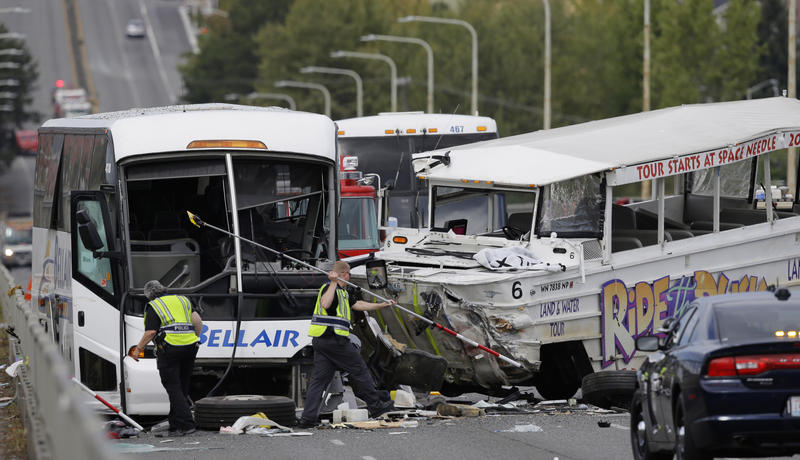 In  Sept. 24, 2015, officials work with the Seattle Police Department following a crash involving a Ride the Ducks amphibious, right,  and a bus, left, that killed four people.