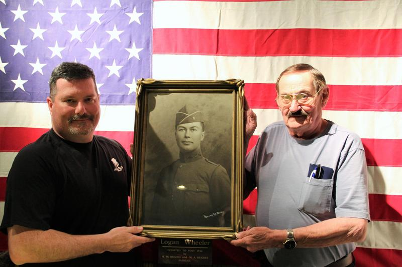 Matt Steadman (left), Sgt At Arms, and Ron Schmidt, commander, hold Logan Wheeler's portrait at the American Legion building in Yakima that bears his name.