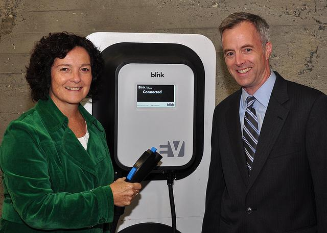 Washington's Secretary of Transporation Paula Hammond and Commerce Secretary Rogers Weed with one of electric vehicle charging stations.