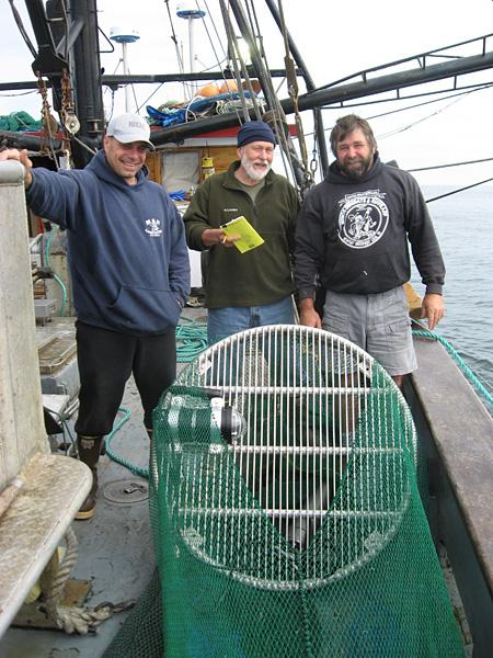 ODFW Biologist Bob Hannah (center) poses with crew members of the Miss Yvonne behind a bycatch reduction device. The tighter spacing on the bars of the device makes it the most effective at reducing bycatch yet.