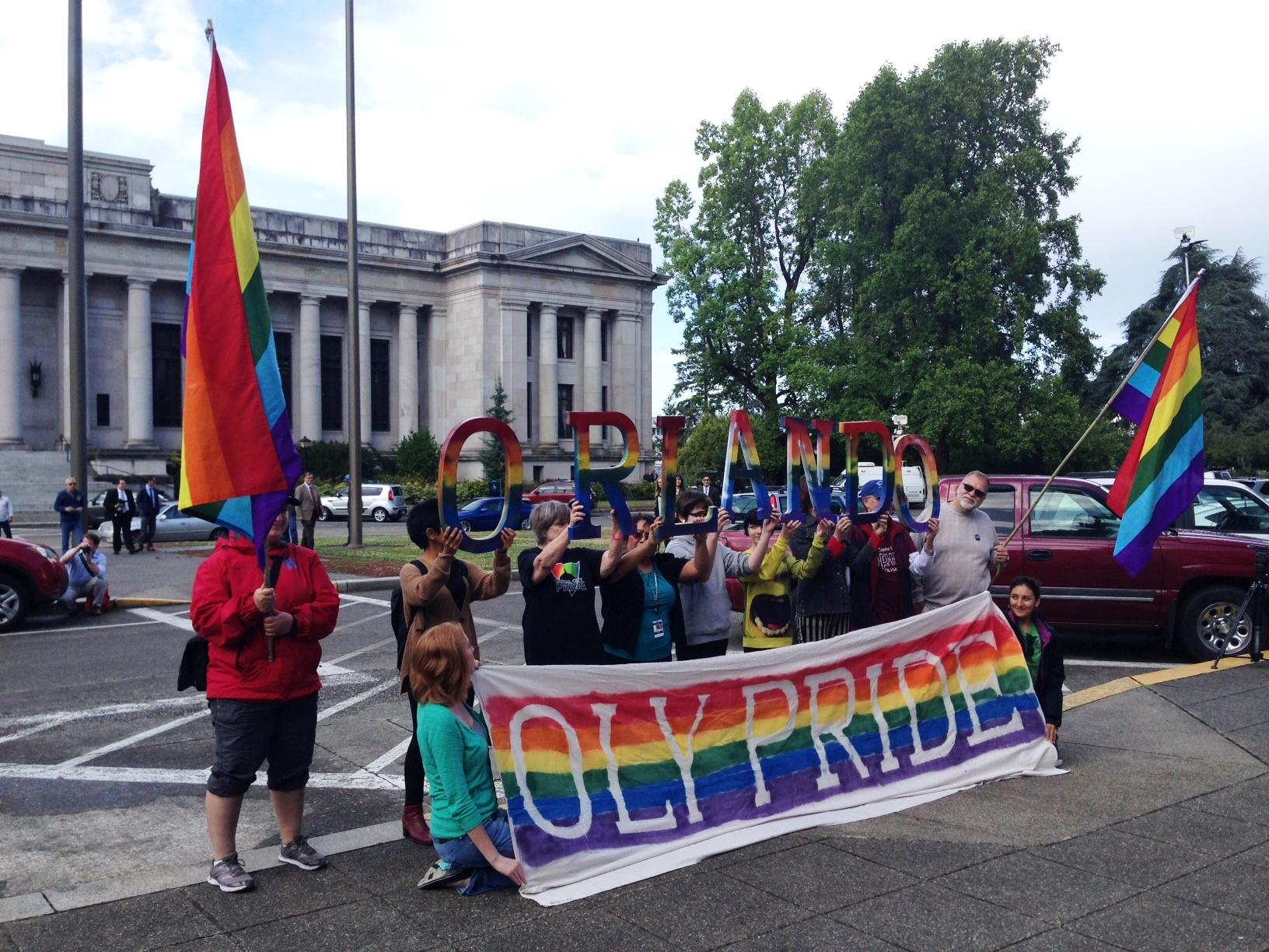 Members of Olympia's LGBT community hold up letters spelling ORLANDO at a flag raising event at the Capitol. Governor Jay Inslee raised the pride flag and then lowered it to half-staff in honor of the victims of last weekend's mass shooting.
