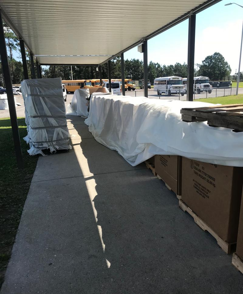About 30 boxes filled with water-damaged classroom materials are lined up outside White Oak High School in Jacksonville on Wednesday, Oct. 3, 2018 for crews to take inventory before they're discarded.