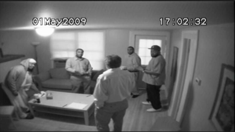 "A still from the film THE NEWBURGH STING shows the ""Newburgh Four"" talking to F.B.I. informant Shahed Hussain (center)."