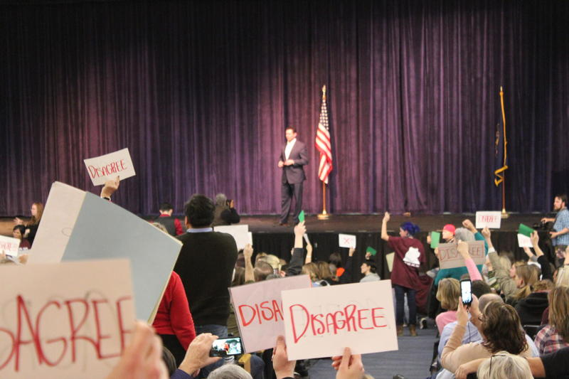 Constituents hold signs up at Rep. Chaffetz's town hall in Cottonwood Heights on Feb. 9, 2016.