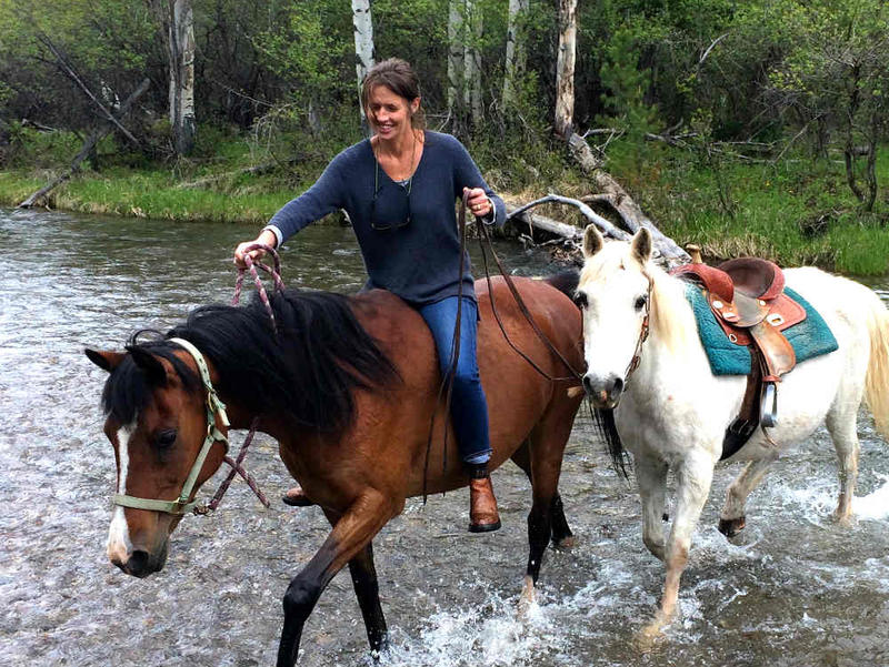 Author Alexandra Fuller on horseback crossing a river.