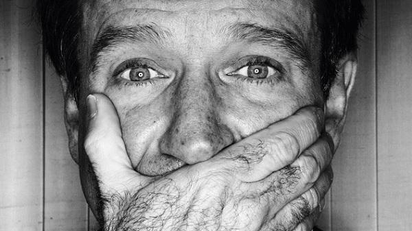 Robin Williams covering mouth with hand.