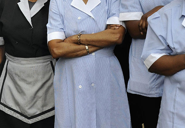 Women of color in maid and other service uniforms.