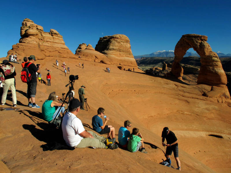 Crowd of people looking at a redrock arch